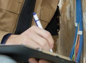 man writing on clipboard
