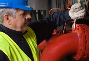 male technician turning nut with wrench on pipe